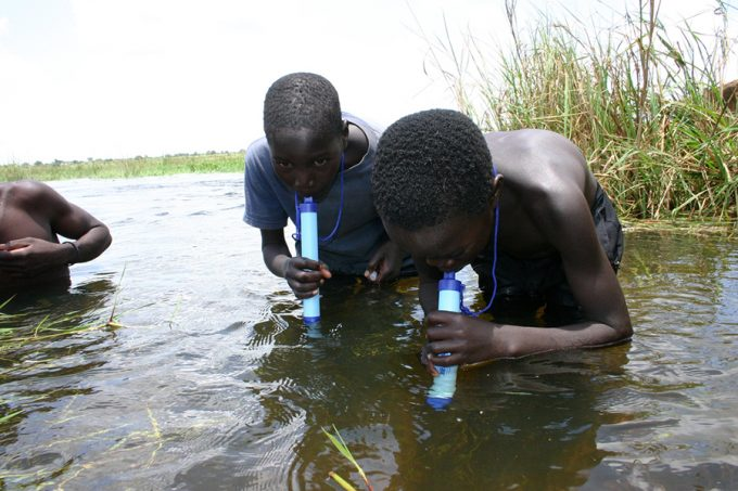 children drinking filthy water with lifestraw