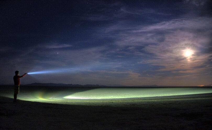 guy holding a LED flashlight over the lake