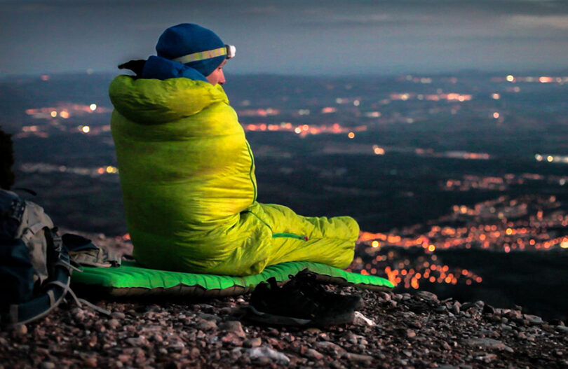 a man in sleeping bag watching over the city