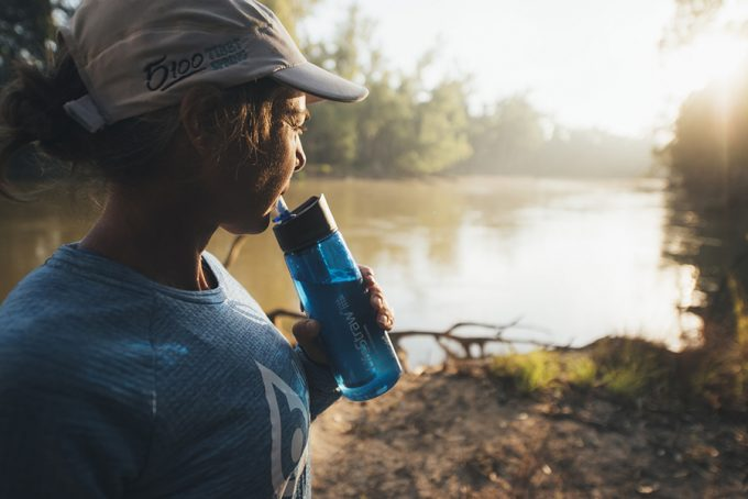 hiker drinking water from lifestraw