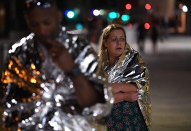 Man and a woman wearing emergency blanket