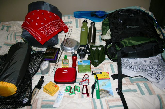 backpacking gear on bed