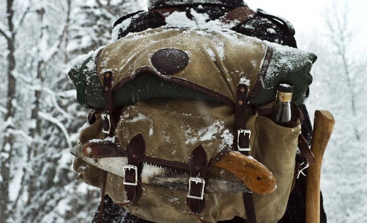 a man with a bug out bag in the winter time