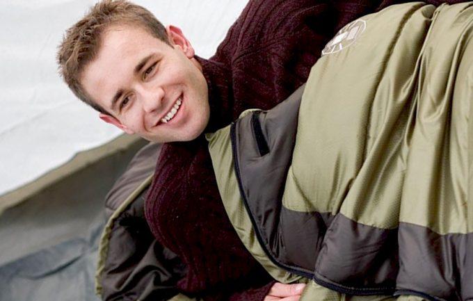 man awake in a sleeping bag