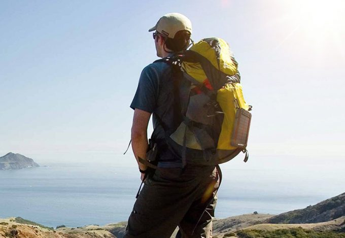 hiker wearing solar charger on backpack