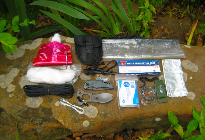 survival kit laid out on rock