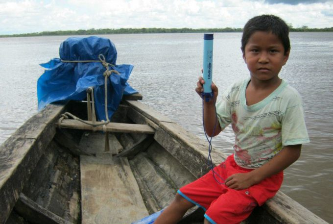 kid holding a lifestraw in boat