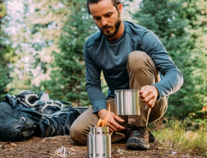 man firing backpacking stove on ground