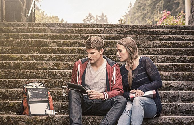 couple sitting next to solar charger