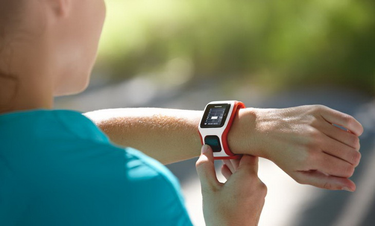 A woman looking at her GPS running watch