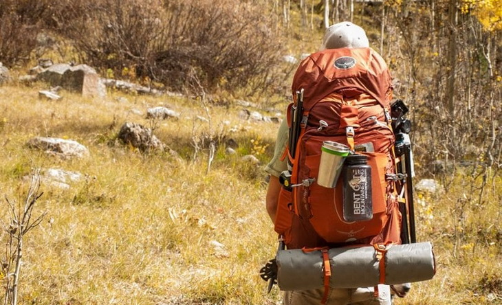 A man with a bug out bag in the summer time