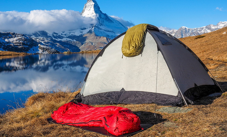 One sleeping bag on a tent and one on the ground and a mountains landscape