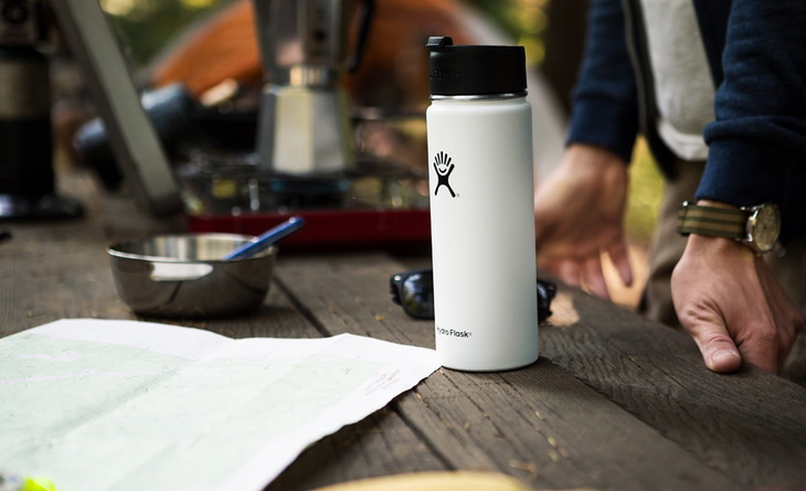 A Vacuum-Insulated-Water-Bottle on a Table next to a manA Vacuum-Insulated-Water-Bottle on a Table next to a man
