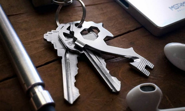 Keychain Multi Tool on table near a laptop and a pair of headphones