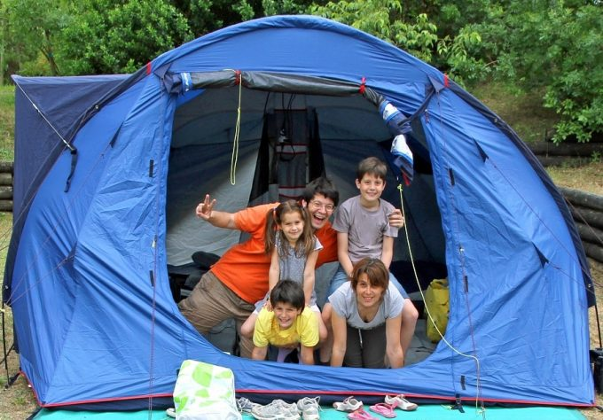family of five in a blue tent camping