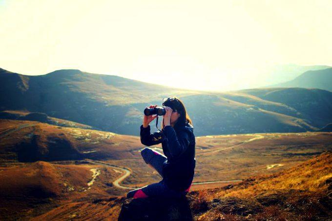 hiker looking trough compact binoculars