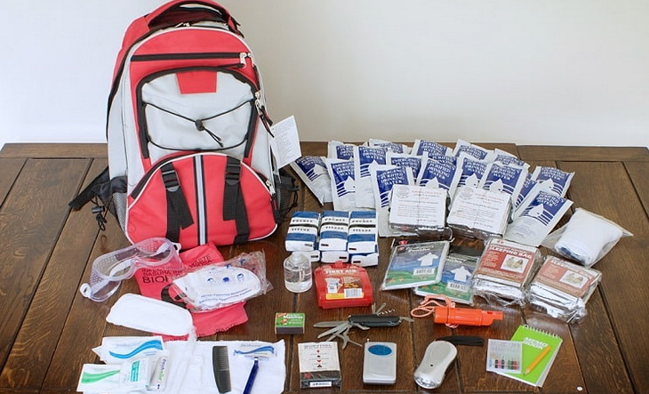 Bug out bag stuffs on a table near a backpack