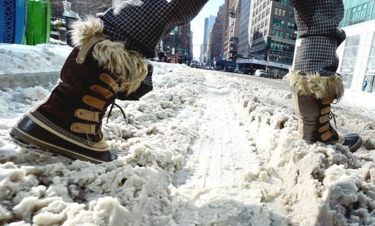 Woman wearing snow boots is passing the street