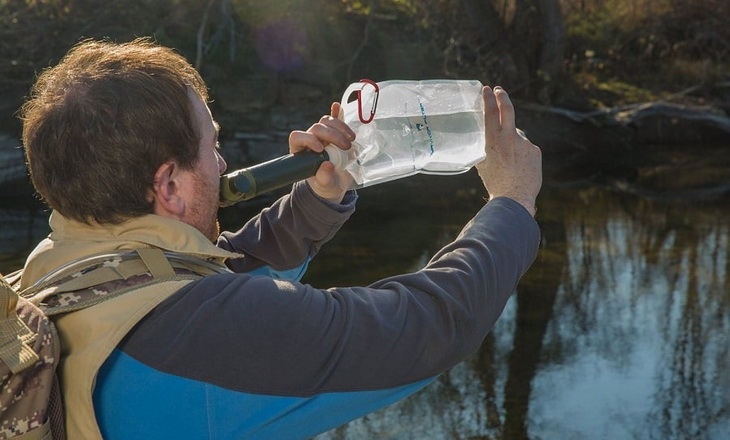 A man drinking water using a survival-water-filter