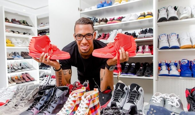 A man in a shoe store holding a pair of sneakers