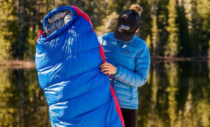 Woman holding a blue sleeping bag