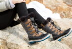 Woman wearing winter hiking boots is getting rest