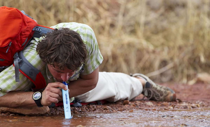 Man drinking water from a river using a survival water filter
