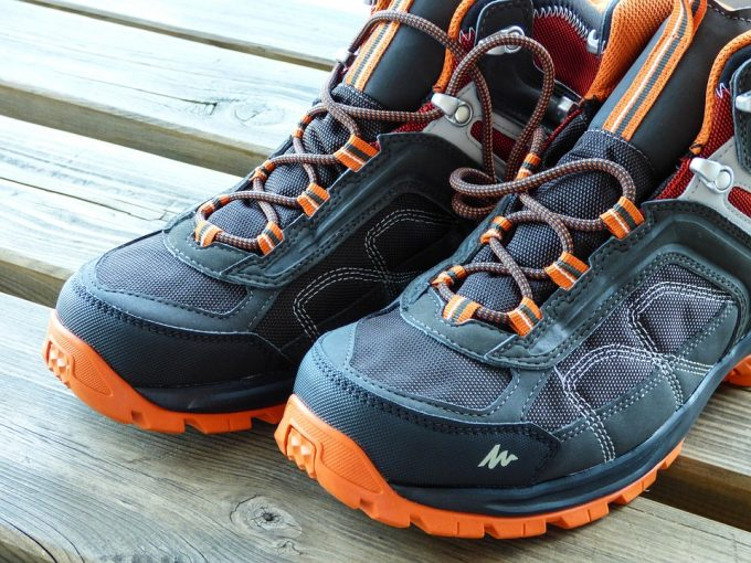 black and orange hiking shoes on wooden table