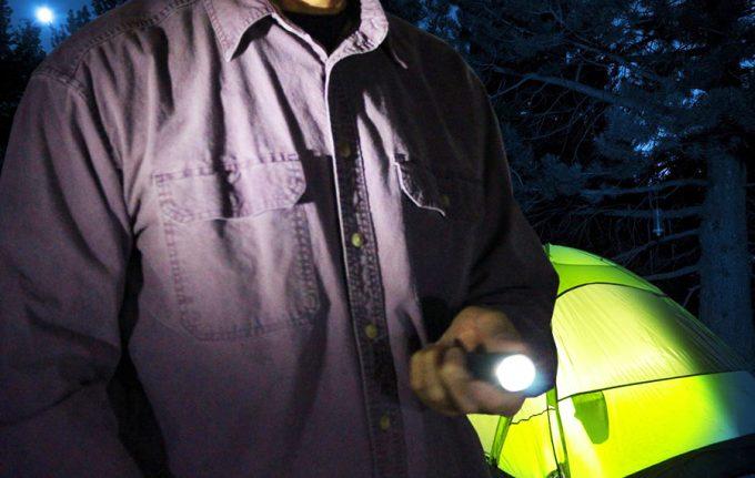 camper holding tactical flashlight