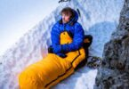 hiker in sleeping bag in snow