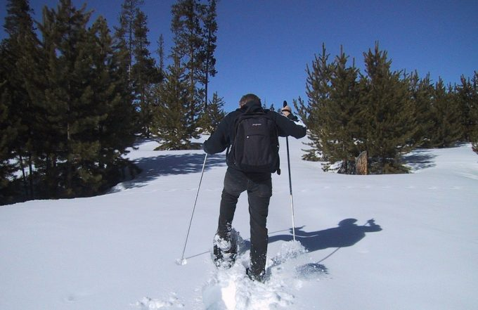 hiker walking with snowshoes on snow
