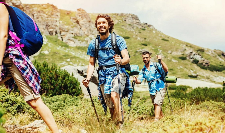 Group of hikers climbing the mountains in the summer time