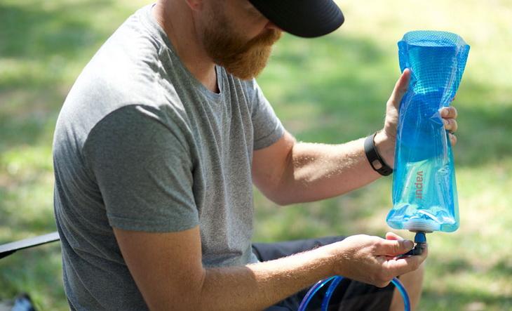 A man holding a Vapur water bottle