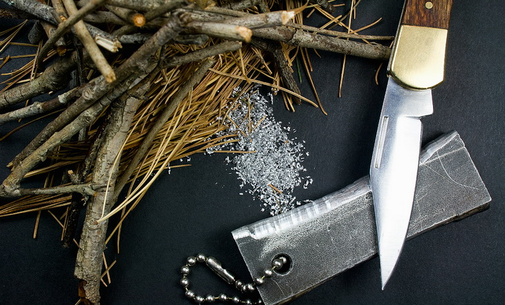 Image presenting magnesium fire starter pocket knife tinder pile