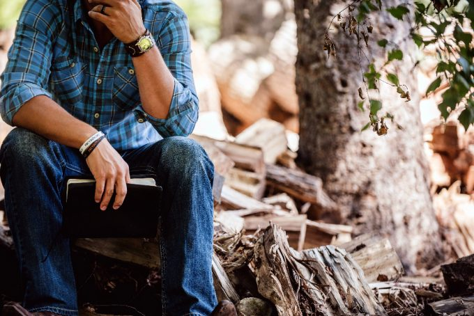 man in the woods wearing survival watch