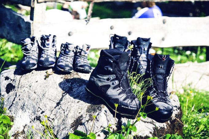 multiple pairs of hiking and backpacking boots in nature
