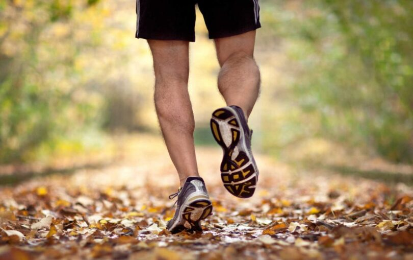 man with runing shoes going trough forest