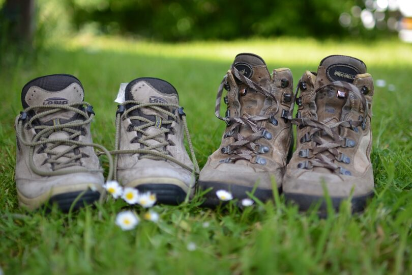 two pairs of hiking boots next to each other in nature