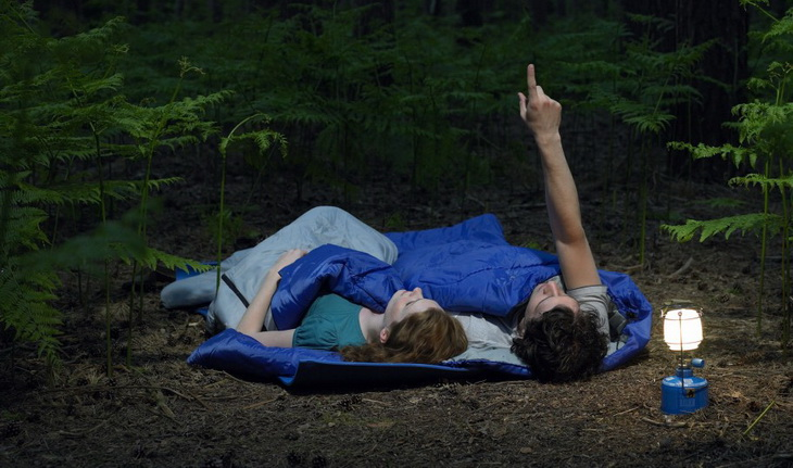 Two adults sharing a double sleeping bag are looking at the stars