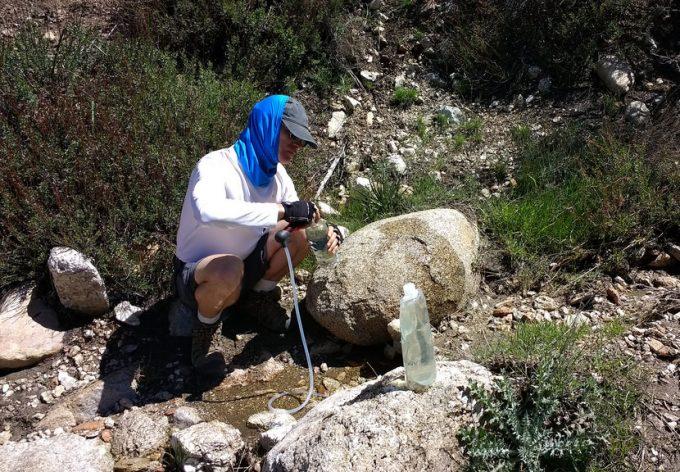 hiker filling water bottle