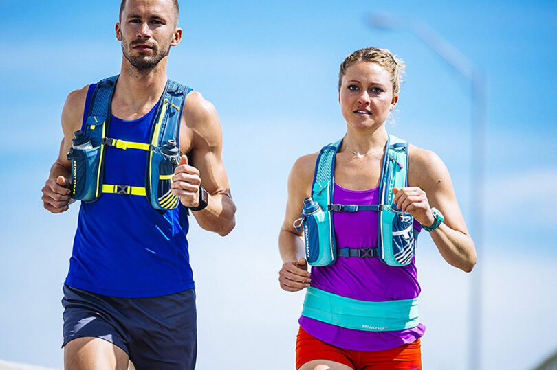 couple running wearing hydration bladders