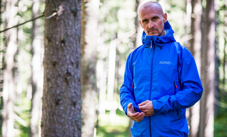 A man wearing Alpkit Balance Hardshell Jacket is looking at the camera