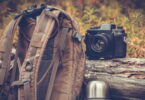 An outdoorretro photo camera next to a backpack and a thermos
