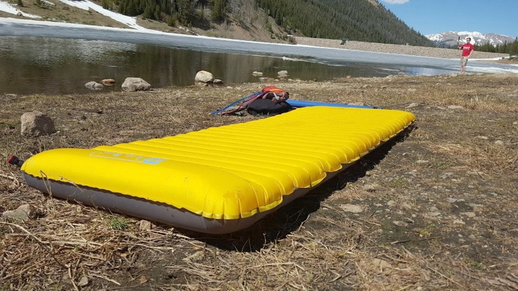 Backpacking-sleeping-pad on the ground near a water