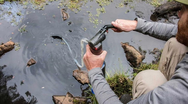 A man filtering the water using a backpacking water filter