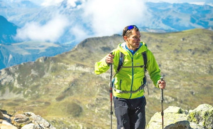 Hiker on top of the mountain wearing 3-in-1-jacket