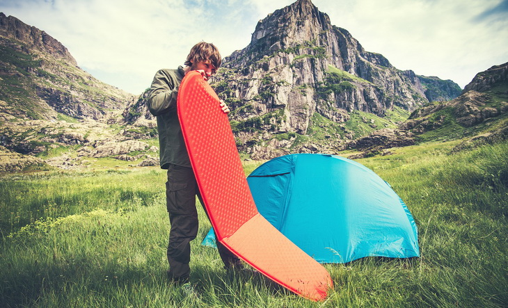 Man Traveler holding red mattress camping equipment and tent outdoor Travel Lifestyle concept rocky mountains landscape on background Summer adventure vacations