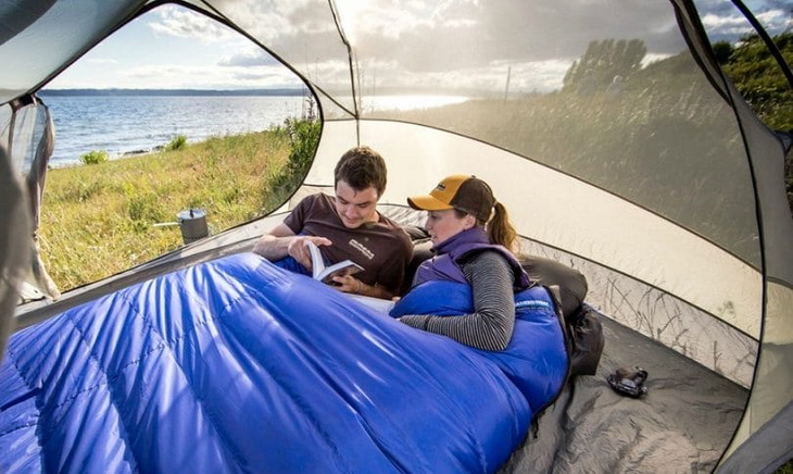Two adults in a double sleeping bag in a tent looking at a book