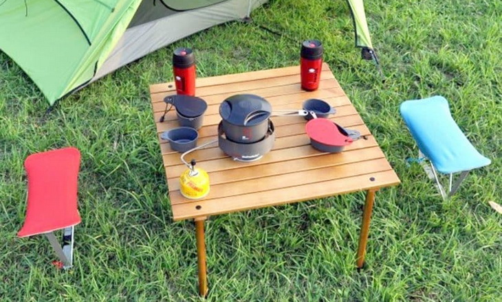 A folding table near a tent in the campsite