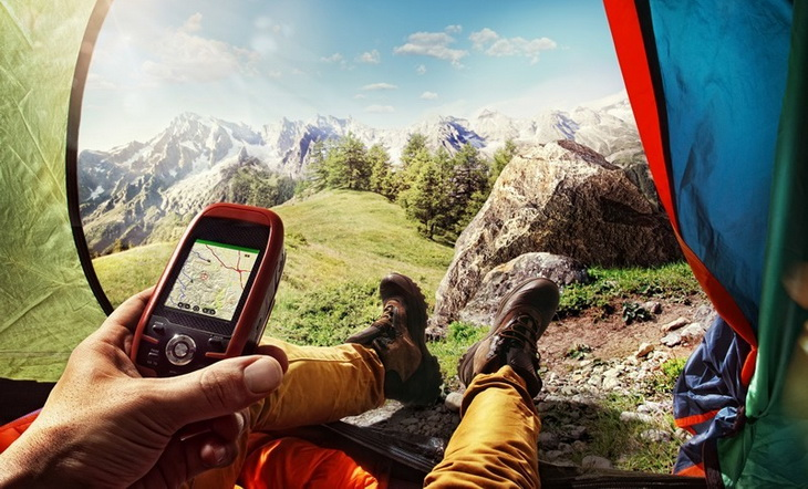 A man in a tent looking at his handheld GPS and a mountain landscape